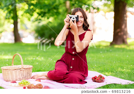 happy woman with camera on picnic at park 69813216