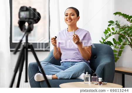 female beauty blogger with camera and lipstick 69813244