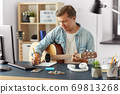 man with guitar writing to music book at home 69813268