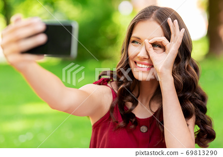 happy woman with smartphone taking selfie at park 69813290
