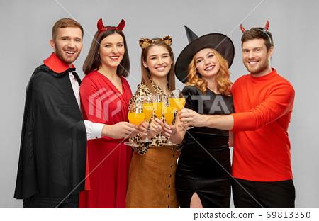 happy friends in halloween costumes over grey 69813350