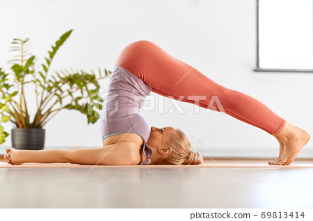 woman doing yoga in plow pose at home 69813414