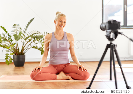 woman with camera streaming for yoga blog at home 69813419