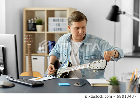 young man with computer playing guitar at home 69813437