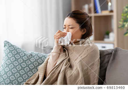 sick asian woman blowing nose with tissue at home 69813460