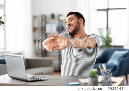 happy man with laptop stretching at home office 69813484