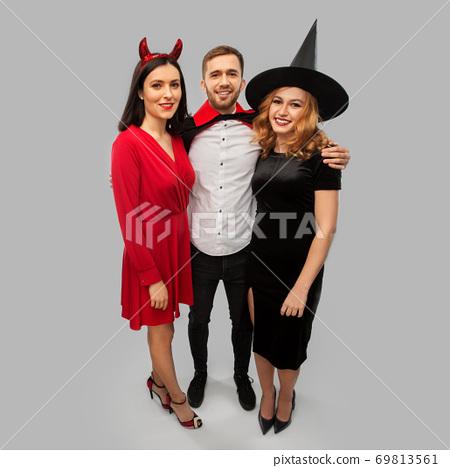 happy friends in halloween costumes over grey 69813561