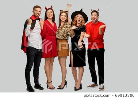 happy friends in halloween costumes over grey 69813586