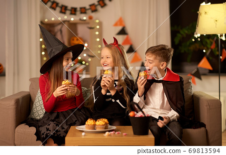 kids in halloween costumes eating cupcakes at home 69813594