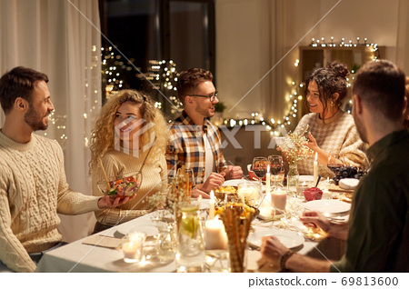 happy friends having christmas dinner at home 69813600