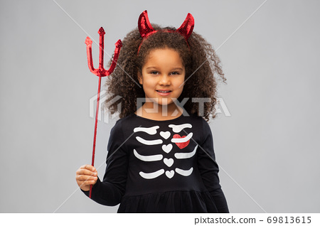 girl with trident and devil's horns on halloween 69813615