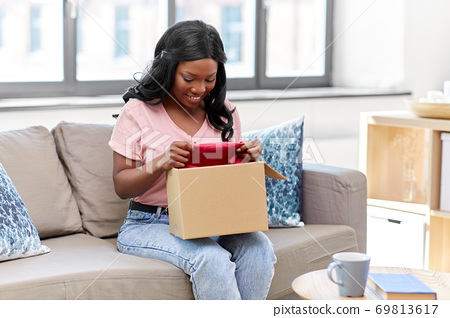 african american woman opening parcel box at home 69813617