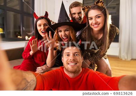 happy friends in halloween costumes taking selfie 69813626