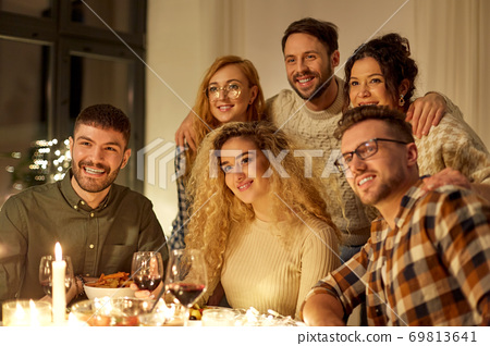 happy smiling friends at christmas dinner party 69813641