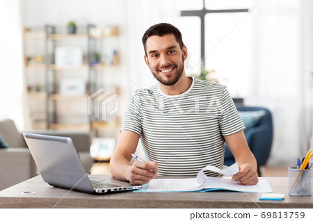 man with papers and laptop working at home office 69813759