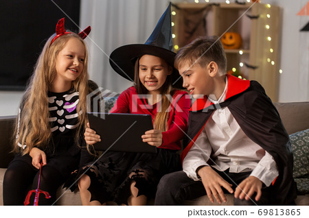 kids in halloween costumes with tablet pc at home 69813865
