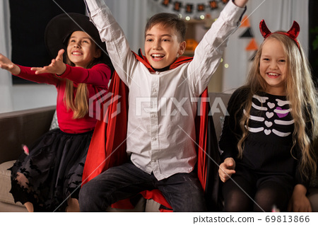 kids in halloween costumes s having fun at home 69813866