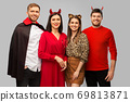 happy friends in halloween costumes over grey 69813871