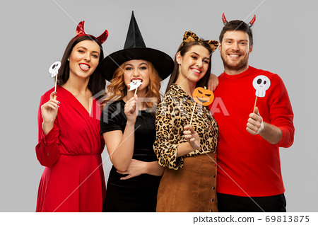 friends in halloween costumes with party props 69813875