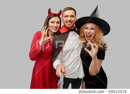 happy friends in halloween costumes taking selfie 69813878