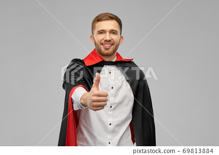 happy man in costume of vampire showing thumbs up 69813884