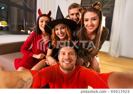 happy friends in halloween costumes taking selfie 69813928
