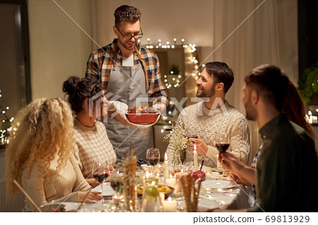 happy friends having christmas dinner at home 69813929