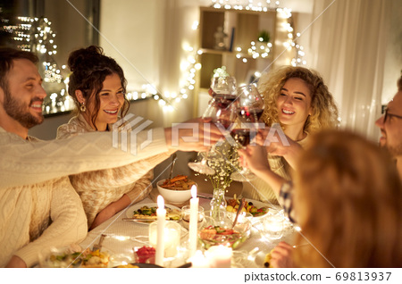 happy friends drinking red wine at christmas party 69813937