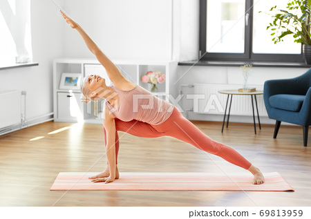woman doing yoga and side angle pose at home 69813959