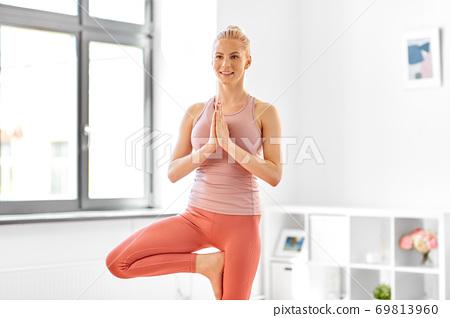 young woman doing yoga tree pose at home 69813960
