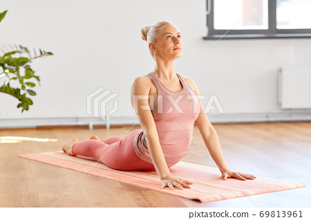 woman doing yoga in cobra pose at home 69813961
