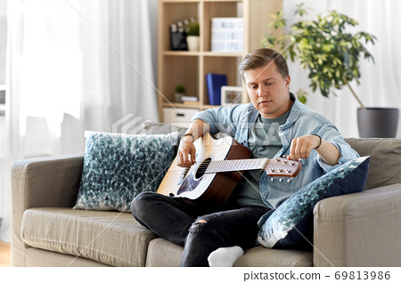 young man playing guitar sitting on sofa at home 69813986