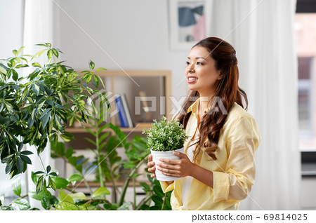 happy asian woman with flower in pot at home 69814025
