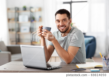 man with laptop drinking coffee at home office 69814050