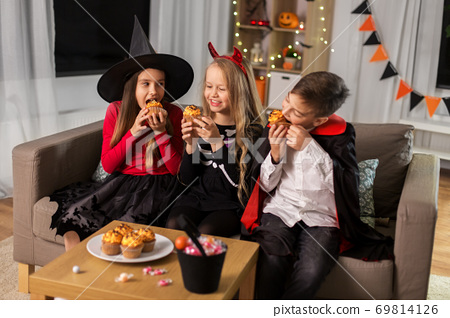 kids in halloween costumes eating cupcakes at home 69814126