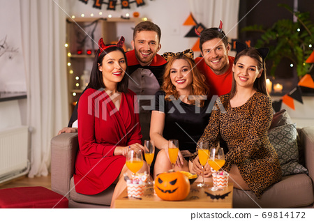 happy friends in halloween costumes at home party 69814172