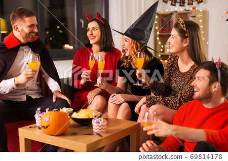 happy friends in halloween costumes at home party 69814178