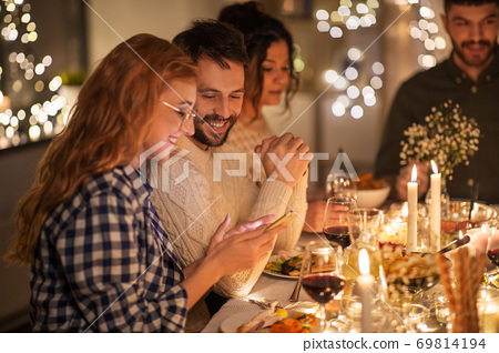 friends with cellphone having dinner party at home 69814194