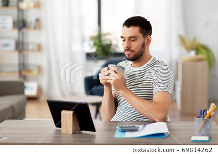man with tablet pc drinking coffee at home office 69814262