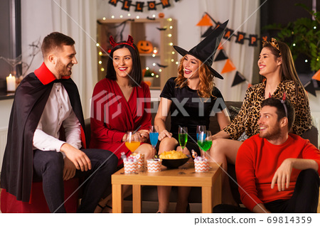 happy friends in halloween costumes at home party 69814359