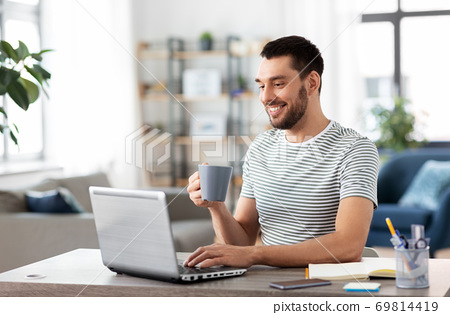 man with laptop drinking coffee at home office 69814419