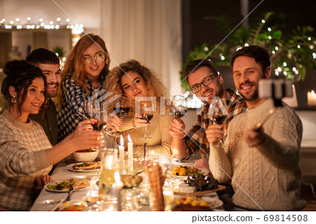 friends taking selfie at christmas dinner party 69814508