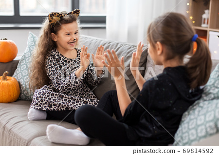 girls in halloween costumes playing game at home 69814592