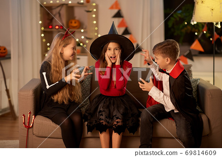 kids in halloween costumes playing at home 69814609