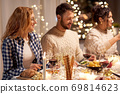 happy friends having christmas dinner at home 69814623