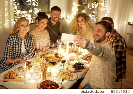 friends taking selfie at christmas dinner party 69814630