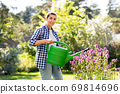 young woman watering flowers at garden 69814696