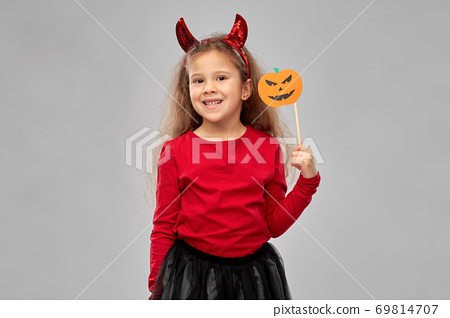 girl in halloween costume with jack-o-lantern 69814707