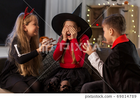 kids in halloween costumes playing at home 69814789