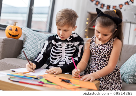 kids in halloween costumes doing crafts at home 69814865